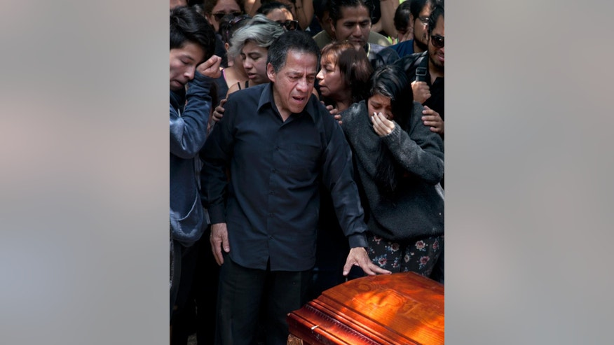 A family member of murdered photojournalist Ruben Espinosa says his last goodbye during his funeral service in Mexico City, Monday, Aug. 3, 2015. With an investigation barely underway, Mexican journalist protection groups are already expressing fears that authorities won't consider Espinosa's brutal killing as being related to his work - even though he fled the state he covered fearing for his safety. Espinosa, 31, worked for the investigative magazine Proceso and other media in Veracruz state. (AP Photo/Marco Ugarte)