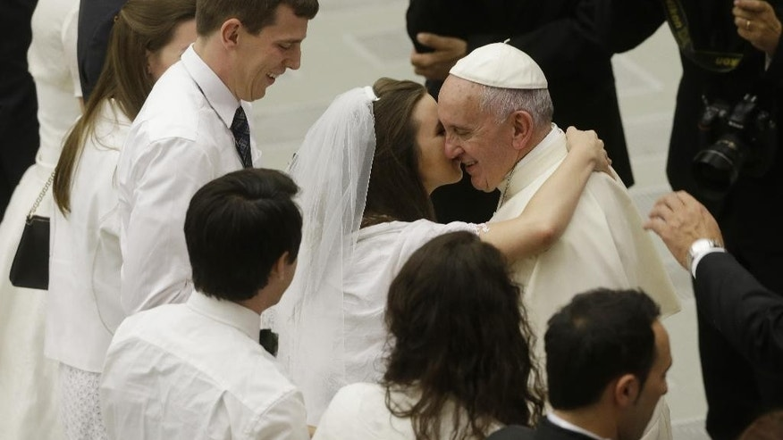 Pope Francis greets newlyweds during the general audience in the Paul VI hall at the Vatican, Wednesday, Aug. 5, 2015. Pope Francis says divorced Catholics who remarry and their children deserve better treatment from the Catholic church. (AP Photo/Gregorio Borgia)