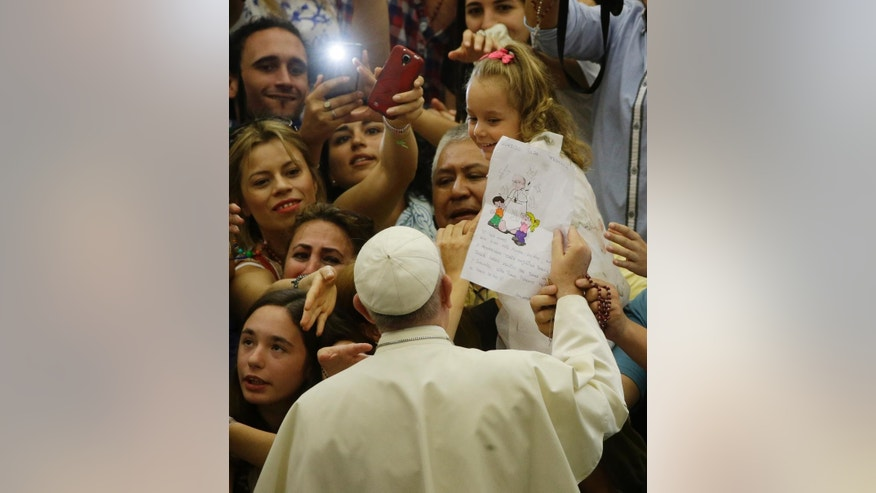 Pope Francis is cheered by faithful as he arrives in the Paul VI hall at the Vatican, Wednesday, Aug. 5, 2015. (AP Photo/Gregorio Borgia)