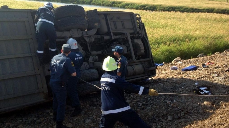 In this handout photo provided by the Far Eastern Branch of the Emergency Situations Ministry, employees fix a rope to a bus, one of the two that collided on a highway linking Khabarovsk, which sits on the border with China, and Komsomolsk-on-Amur, Russia, Wednesday, Aug. 5, 2015. Russian health officials say two buses have collided in the far east of the country, killing at least 16 people and injuring more than 50 others. The agency has opened a probe into the alleged violation of traffic rules.  (Far Eastern Branch of Emergency Situations Ministry Press Service via AP)