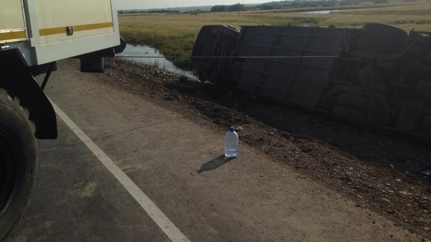 In this handout photo provided by the Far Eastern Branch of the Emergency Situations Ministry, a truck pulls a bus, one of the two that collided on a highway linking Khabarovsk, which sits on the border with China, and Komsomolsk-on-Amur, Russia, Wednesday, Aug. 5, 2015. Russian health officials say two buses have collided in the far east of the country, killing at least 16 people and injuring more than 50 others. The agency has opened a probe into the alleged violation of traffic rules.  (Far Eastern Branch of Emergency Situations Ministry Press Service via AP)