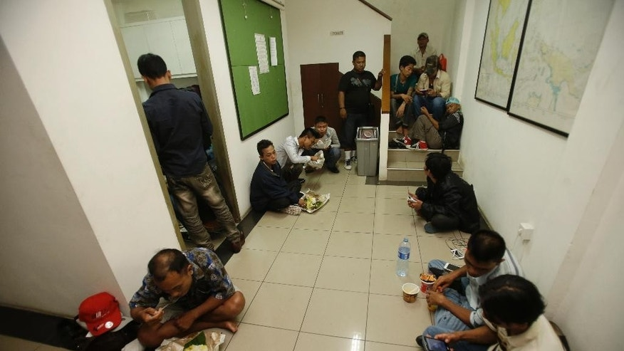 In this late Wednesday, Aug. 5, 2015 photo, Burmese fishermen, part of a group of 45 men who were rescued by Indonesian Police, have their dinner at the National Police headquarters in Jakarta. The police rescued the fishermen, believed to be trafficking victims, from a hotel in central Jakarta where they were taken after traveling on fake documents, officials and the men said Thursday. (AP Photo/Achmad Ibrahim)