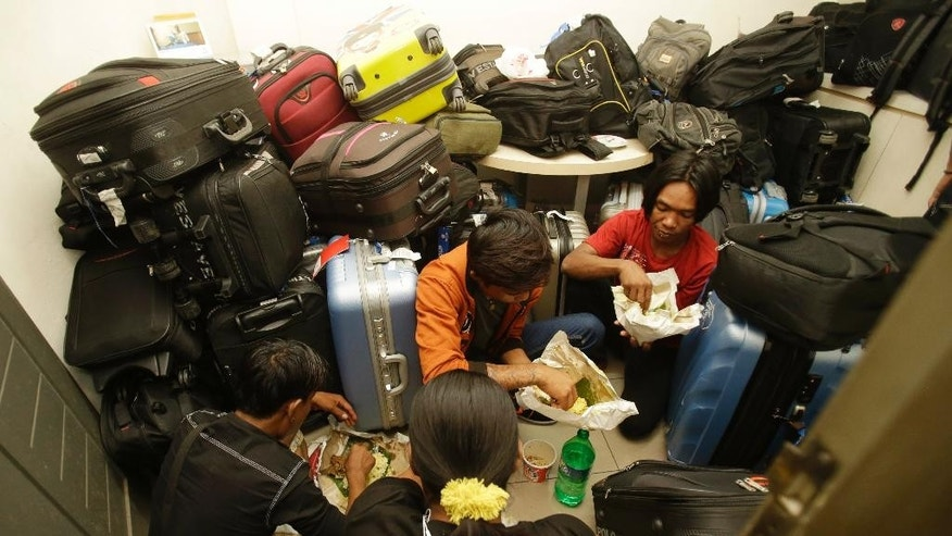 In this late Wednesday, Aug. 5, 2015 photo, Burmese fishermen, part of a group of 45 men who were rescued by Indonesian Police, have their dinner among their belongings at the National Police headquarters in Jakarta, Indonesia. The police rescued the fishermen, believed to be trafficking victims, from a hotel in central Jakarta where they were taken after traveling on fake documents, officials and the men said Thursday. (AP Photo/Achmad Ibrahim)