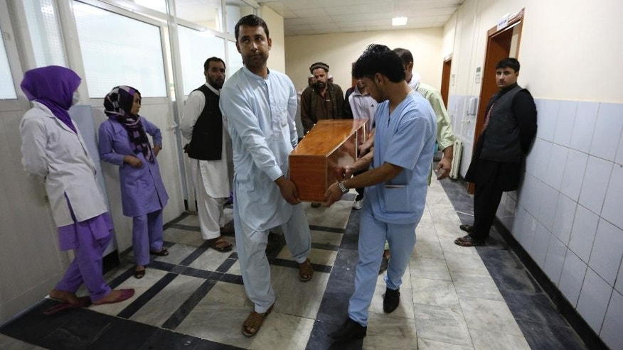 Hospital workers carry the dead body of a victim in a car bomb attack in Kabul, Afghanistan, Friday, Aug. 7, 2015. A bomb hidden in a truck exploded in the center of the Afghan capital. Police chief Abdul Rahman Rahimi said the pre-dawn blast was near a Defense Ministry compound, but that all of the victims were civilians, including women and children. (AP Photo/Rahmat Gul)