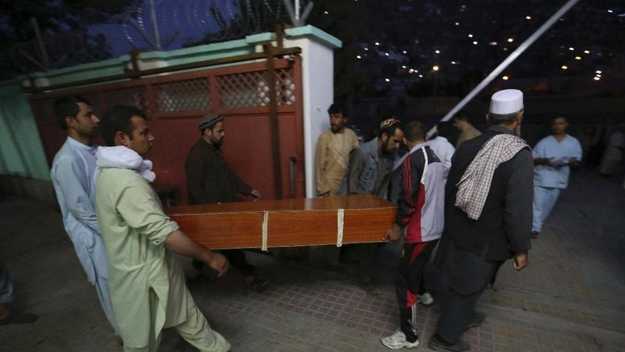 Afghans carry the dead body of a victim after a car bomb attack in Kabul, Afghanistan, Friday, Aug. 7, 2015. A bomb hidden in a truck exploded in the center of the Afghan capital. Police chief Abdul Rahman Rahimi said the pre-dawn blast was near a Defense Ministry compound, but that all of the victims were civilians, including women and children. (AP Photo/Rahmat Gul)