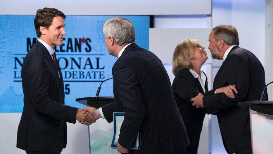 Leaders of Canada's four political parties, Liberal leader Justin Trudeau, left, shakes hands with Conservative leader Stephen Harper as Green party leader Elizabeth May, second from right, and New Democrat leader Thomas Mulcair embrace following the first leaders debate Thursday, Aug. 6, 2015, in Toronto. (Frank Gunn/The Canadian Press via AP) MANDATORY CREDIT