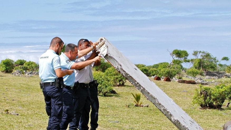 FILE - In this July 29, 2015 file photo, French police officers inspect a piece of debris from a plane in Saint-Andre, Reunion Island. Confirmation that a wing flap found on an island in the western Indian Ocean is part of Malaysia Airlines Flight 370 would add a critical piece to the puzzle of the Boeing 777's disappearance 17 months ago. Malaysian Prime Minister Najib Razak delivered that confirmation Thursday, Aug. 6, 2015 though French, U.S. and Australian investigators stopped just short of that, saying the part is from a 777 and acknowledging that Flight 370 is the only 777 missing. Examination of the part is continuing.  (AP Photo/Lucas Marie, File)