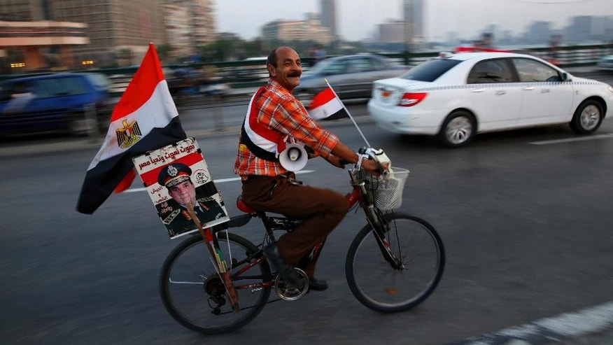 A supporter of Egyptian President Abdel-Fattah el-Sissi carries his poster on his bike as he celebrates with others for Thursday's opening of the new extension of the Suez Canal, riding on the Qasr El Nile Bridge in Cairo, Egypt, Wednesday, Aug. 5, 2015. Egypt will unveil a major extension of the Suez Canal on Thursday, a mega-project that has emerged as a cornerstone of el-Sissi's efforts to restore national pride and revive the economy after years of unrest. (AP Photo/Hassan Ammar)