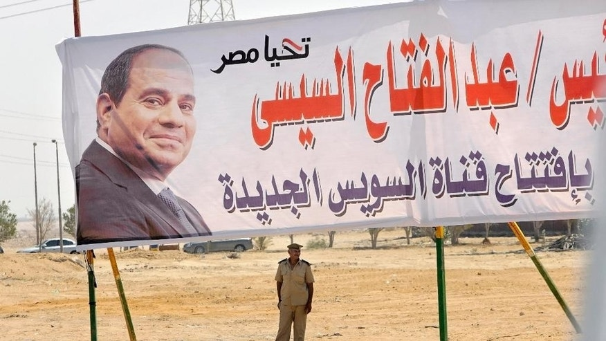 "A policeman stands alert under a billboard with the photo of Egyptian President Abdel-Fattah el-Sissi at the Cairo-Ismailia desert road in Egypt, Thursday, Aug. 6, 2015. Egypt is to unveil a major extension of the Suez Canal that el-Sissi has billed as a historic achievement that will boost the economy following years of unrest. Arabic reads, ""long live Egypt, President Abdel-Fattah el-Sissi, opening of the new Suez canal."" (AP Photo/Amr Nabil)"
