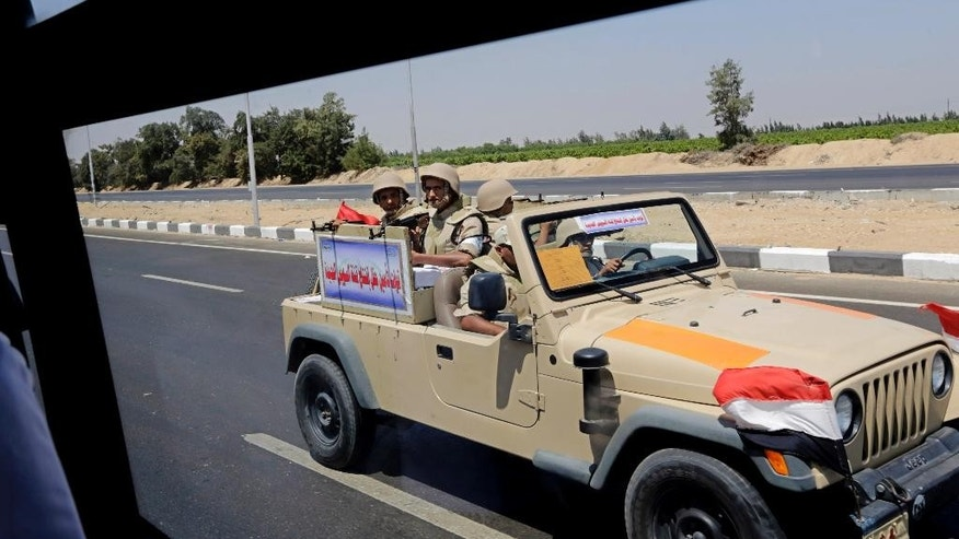 "Egyptian army soldiers patrol the Cairo-Ismailia desert road in Egypt, Thursday, Aug. 6, 2015. Egypt is to unveil a major extension of the Suez Canal that el-Sissi has billed as a historic achievement that will boost the economy following years of unrest. Arabic on the army vehicle reads, ""forces securing the inauguration ceremony of the new Suez canal."" (AP Photo/Amr Nabil)"