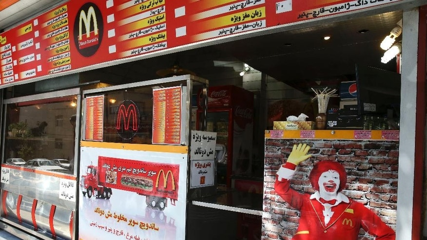 """In this Wednesday, Aug. 5, 2015 photo, Iran's fast food restaurant """"Mash Donald's,"""" a knock-off version of McDonald's, sells burgers and fries in western Tehran, Iran. Businesses worldwide want to get into Iran, home to some 80 million people, oil and gas reserves and a middle class eager for familiarity with brands based in the U.S. (AP Photo/Vahid Salemi)"""