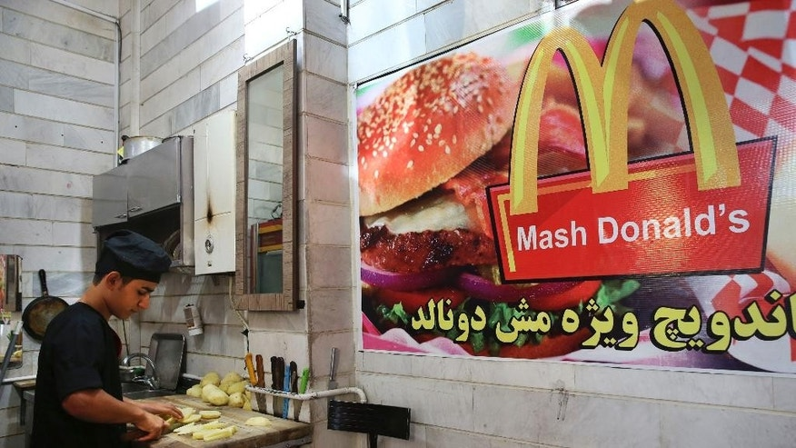 """In this Wednesday, Aug. 5, 2015 photo, Iranian worker Shahin Mirouzadeh cuts potatoes at """"Mash Donald's"""" fast food restaurant, a knock-off version of McDonald's in western Tehran, Iran. Businesses worldwide want to get into Iran, home to some 80 million people, oil and gas reserves and a middle class eager for familiarity with brands based in the U.S. Though hard-liners worry that could corrupt the Islamic nation, others have opened their mind to the idea of having them around. (AP Photo/Vahid Salemi)"""