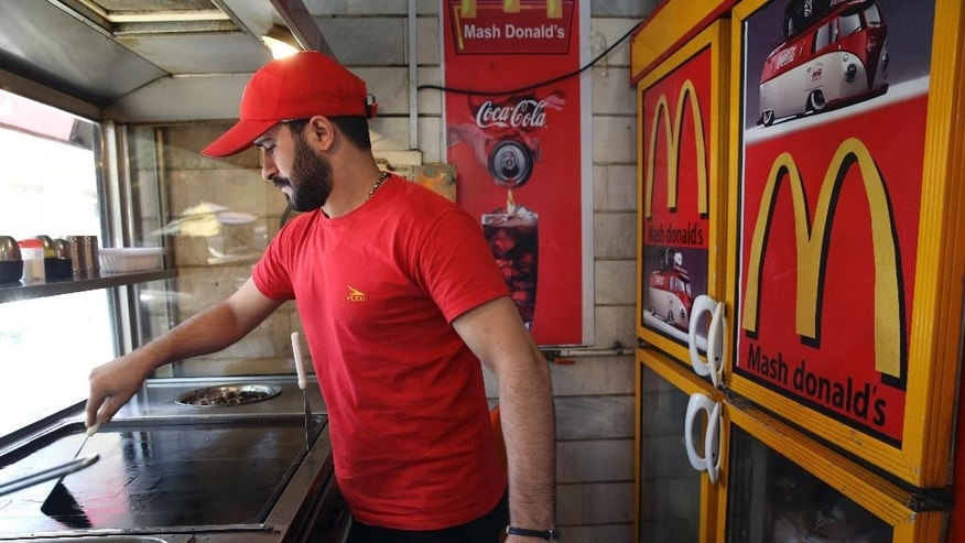 """In this Wednesday, Aug. 5, 2015 photo, Iranian worker Karim Jalalpour cleans the kitchen at """"Mash Donald's"""" fast food restaurant, a knock-off version of McDonald's in western Tehran, Iran. The owner of the business welcomes the competition with McDonald's. """"They should be allowed to come,"""" restaurateur Hassan Padiav said. """"What is the reason for all the opposition? Nothing bad would happen.""""  (AP Photo/Vahid Salemi)"""