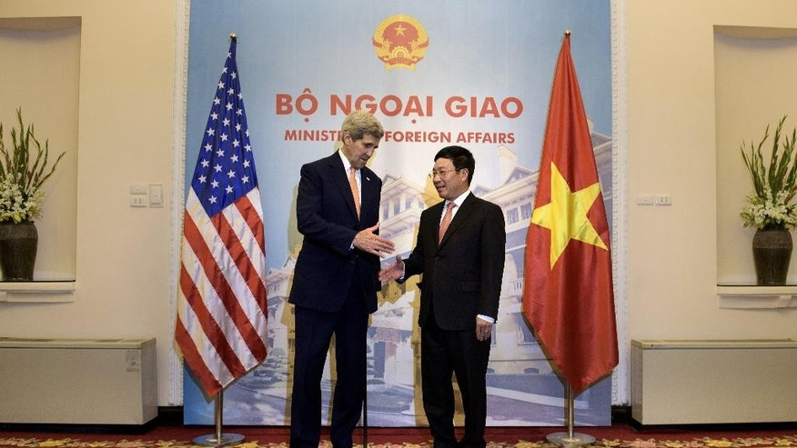 U.S. Secretary of State John Kerry, left, and Vietnam's Foreign Minister Pham Binh Minh shake hands before a meeting at the Foreign Ministry in Hanoi, Vietnam Friday, April 7, 2015. Kerry on Friday extolled the virtues of reconciling with former enemies as he marked the 20th anniversary of diplomatic relations between the United States and Vietnam. (Brendan Smialowski/Pool Photo via AP)