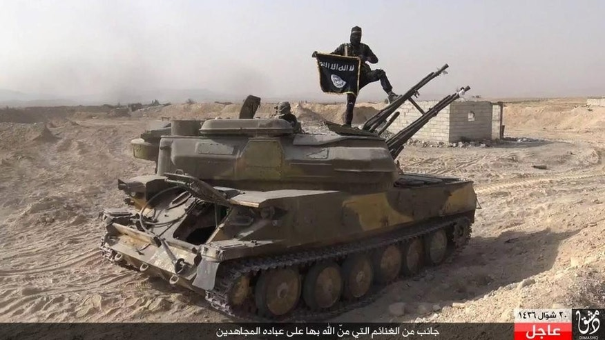 In this picture released on Wednesday, Aug. 5, 2015 by the Rased News Network a Facebook page affiliated with Islamic State militants, an Islamic State militant holds the group's flag as he stands on a tank they captured from Syrian government forces, in the town of Qaryatain southwest of Palmyra, central Syria. The Islamic State group on Thursday seized a key town in central Syria following heavy clashes with President Bashar Assad's forces, in the militants' biggest advance since capturing the historic town of Palmyra in May, Syrian activists said. (Rased News Network a Facebook page affiliated with Islamic State militants via AP)