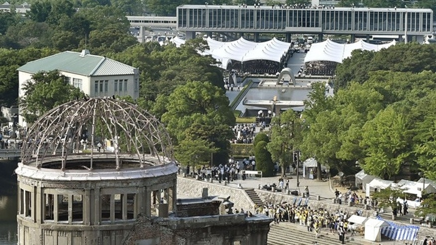 August 6, 2015: The Atomic Bomb Dome stands in front as a ceremony to mark the 70th anniversary of the atomic bombing of Hiroshima is held at the Hiroshima Peace Memorial Park, seen in the center, in Hiroshima, Japan. (Kyodo Photo via AP)