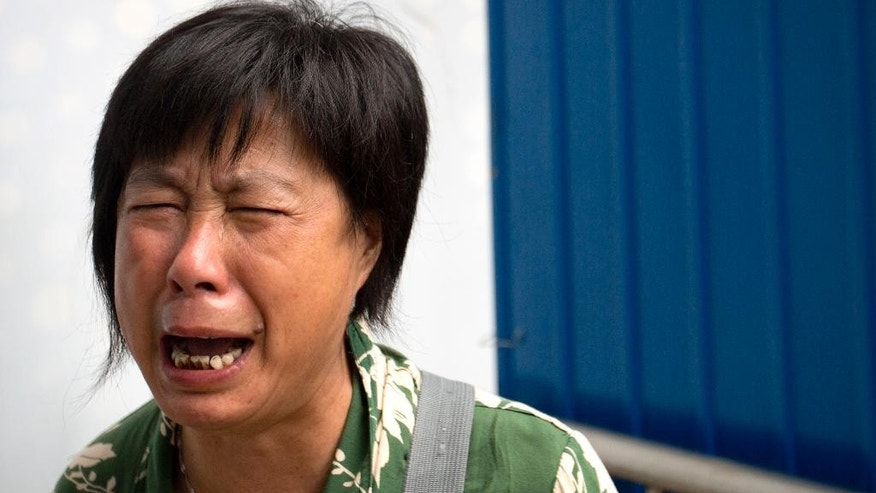 Bao Lanfang, whose daughter-in-law, son, and granddaughter were aboard Malaysia Airlines Flight 370, cries as she protests outside the company's offices in Beijing, Thursday, Aug. 6, 2015. About a dozen Chinese relatives of passengers protested outside the Malaysia Airlines offices in Beijing on Thursday. Families aching for closure after their relatives disappeared aboard Malaysia Airlines Flight 370 last year vented their deep frustration Thursday at conflicting signals from Malaysia and France over whether the finding of a plane part had been confirmed. (AP Photo/Mark Schiefelbein)