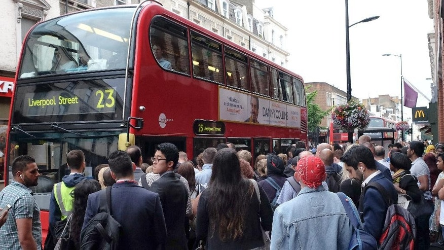 Passengers crowd around a bus stop outside Paddington Station in London, Thursday, Aug. 6, 2015. Commuters are having to find alternative methods of travel Thursday as the London tubes are not running due to a strike. London's mayor has ruled out offering more money to resolve a London Underground labor set to shut down services for the second time this summer. (AP Photo/Kirsty Wigglesworth)