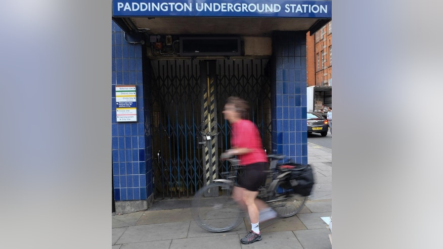 A cyclist passes a locked entrance to Paddington tube station in London, Thursday, Aug. 6, 2015. Commuters are having to find alternative methods of travel Thursday as the London tubes are not running due to a strike. London's mayor has ruled out offering more money to resolve a London Underground labor set to shut down services for the second time this summer. (AP Photo/Kirsty Wigglesworth)