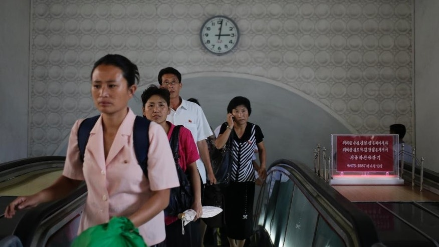 """FILE - In this Sept. 1, 2014, photo, a clock hangs on the wall as North Koreans leave an underground train station in Pyongyang, North Korea. North Korea said Friday, Aug. 7, 2015, that it will establish its own time zone next week by pulling back its current standard time by 30 minutes. Local time in North and South Korea and Japan is the same — nine hours ahead of GMT. It was set during Japan's rule over what was single Korea from 1910 to 1945. The establishment of """"Pyongyang time"""" is meant to root out the legacy of the Japanese colonial period, the North's official Korean Central News Agency said. (AP Photo/Wong Maye-E, File)"""