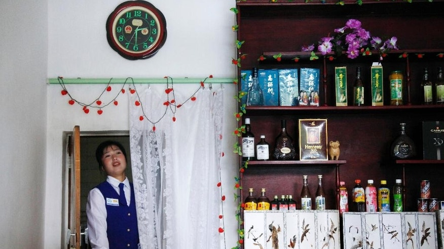 """FILE - In this Aug. 29, 2011, photo, a North Korean waitress walks through a door under a clock with Chinese emblems at a restaurant in Rason city in North Korea. North Korea said Friday, Aug. 7, 2015, that it will establish its own time zone next week by pulling back its current standard time by 30 minutes. Local time in North and South Korea and Japan is the same — nine hours ahead of GMT. It was set during Japan's rule over what was single Korea from 1910 to 1945. The establishment of """"Pyongyang time"""" is meant to root out the legacy of the Japanese colonial period, the North's official Korean Central News Agency said. (AP Photo/Ng Han Guan, File)"""