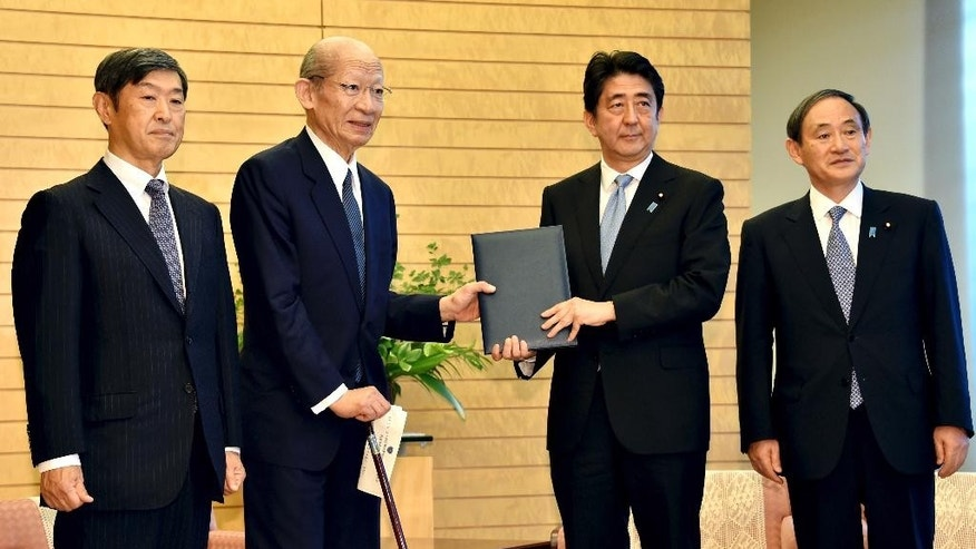 Japanese Prime Minister Shinzo Abe, second right, accompanied by Chief Cabinet Secretary Yoshihide Suga, right, poses as he receives a 38-page report from Taizo Nishimuro, second left, chairman of the Japanese government's advisory panel on the history of the 20th century and on Japan's role and the world order in the 21st century, and Shinichi Kitaoka, deputy of the panel, at Abe's office in Tokyo Thursday, Aug. 6, 2015. The government panel commissioned by Abe to review the country's recent history has praised Japan's postwar economic growth and commitment to pacifism but also cites lack of reconciliation with China and South Korea. The report released Thursday did not specify what Abe should say in his statement marking the 70th anniversary of the end of World War II later this month, or whether he should use the same language to convey the apology from 1995 by then-Prime Minister Tomiichi Murayama. However, the report urged sensitivity for the feelings of the victims of Japan's wartime actions. (Yoshikazu Tsuno/Pool Photo via AP)