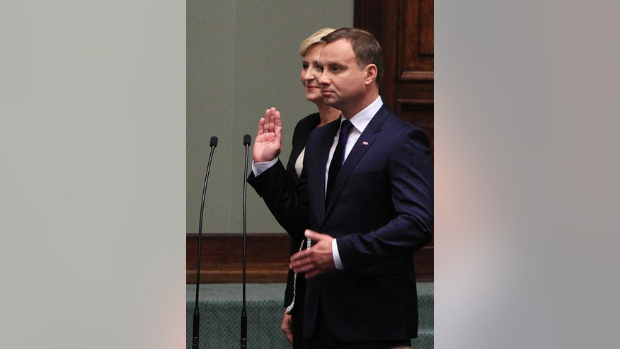 New Polish President Andrzej Duda,right, takes the oath during the inauguration ceremony at the Parliament as his wife Agata stands next to him, in Warsaw, Poland, Thursday, Aug. 6, 2015. (AP Photo/Czarek Sokolowski)