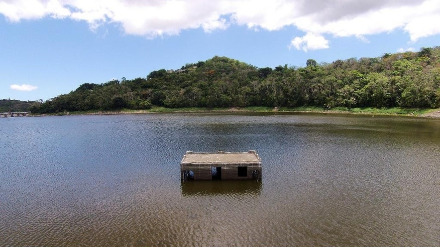 A home, once part of a community before the area was submerged by the Carraizo reservoir, sits partially uncovered due to a drought in Trujillo Alto, Puerto Rico, Wednesday, Aug. 5, 2015. The severe drought in Puerto Rico is forcing businesses to temporarily close, public schools to cancel breakfast service and people to find creative ways to stay clean amid sweltering temperatures. (AP Photo/Ricardo Arduengo)