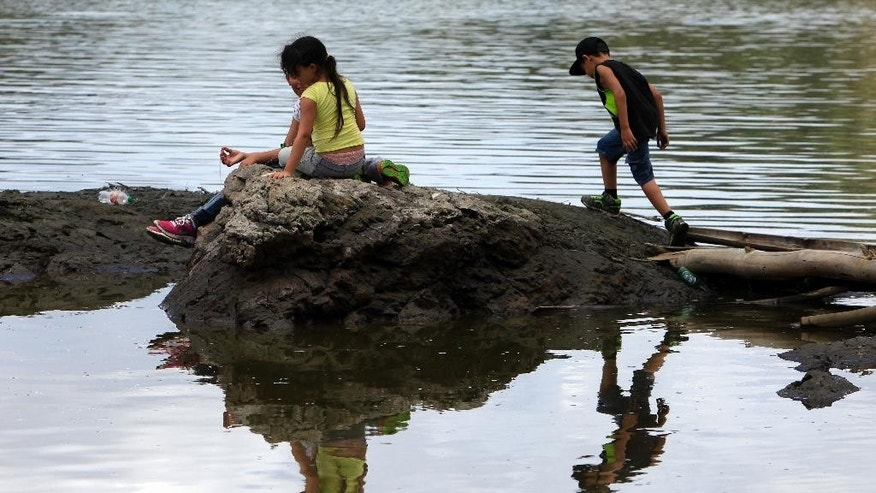 Children play on land partially exposed caused by a drought at the Carraizo reservoir in Trujillo Alto, Puerto Rico, Wednesday, Aug. 5, 2015. Due to the severity of the drought, rationing rules that had meant water coming through the pipes only one day out of three will increase the cutoff to one day out of four starting next week, government officials say. (AP Photo/Ricardo Arduengo)