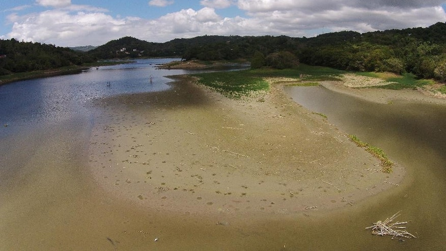 This aerial photo shows the drought affected Carraizo reservoir in Trujillo Alto, Puerto Rico, Wednesday, Aug. 5, 2015. The drought is one of the worst in the U.S. territory's history. July was the fourth driest month in the capital of San Juan since 1898, the year Puerto Rico became a possession of the United States. (AP Photo/Ricardo Arduengo)