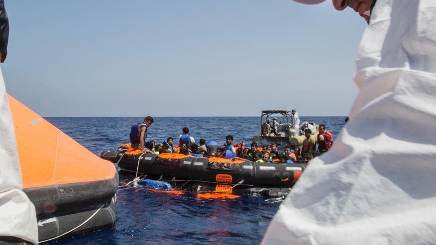 Survivors of the capsizing and sinking of a fishing boat crowded with migrants are brought aboard Irish and Italian Navy life-boats to the Dignity I MSF search and rescue vessel which responded to the emergency in the Mediterranean sea off Libya, Wednesday, Aug. 5, 2015. The Italian coast guard and Irish navy said at least 367 people were saved, although 25 bodies also were found in the latest human smuggling tragedy. (Marta Soszynska/MSF via AP)