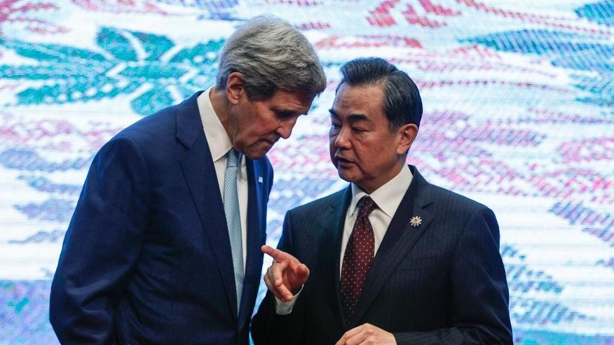 U.S. Secretary of State John Kerry, left, and Chinese Foreign Minister Wang Yi, chat after the group photo session before the East Asia Summit Foreign Ministers' Meeting in Kuala Lumpur, Malaysia on Thursday, Aug. 6, 2015. (AP Photo/Joshua Paul)