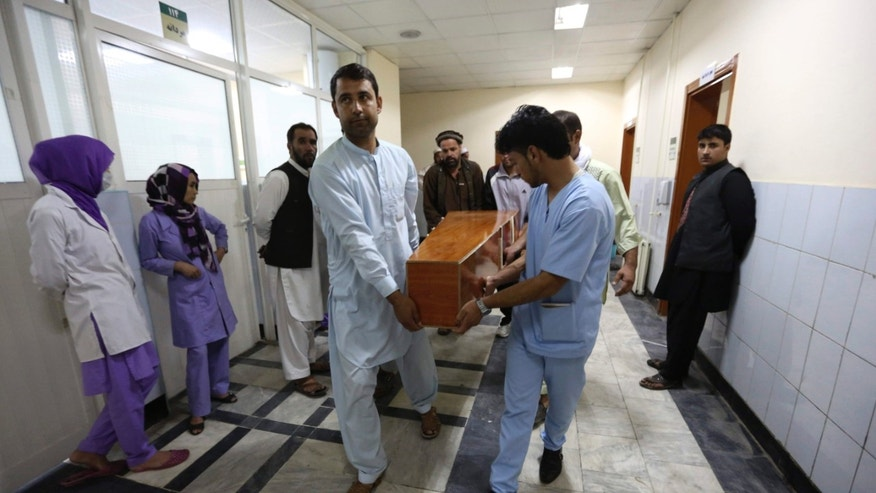 Aug. 7, 2015: Hospital workers carry the dead body of a victim in a car bomb attack in Kabul, Afghanistan.