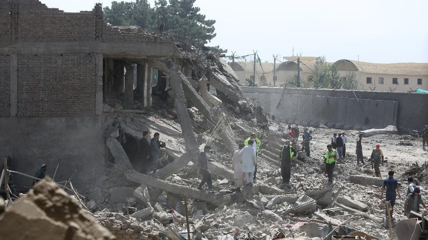 Afghan security personnel inspect the site of a car bomb attack in Kabul, Afghanistan, Friday, Aug. 7, 2015. A bomb hidden in a truck exploded in the center of the Afghan capital, killing several people and wounding hundreds, police and health officials said Friday. Police chief Abdul Rahman Rahimi said the pre-dawn blast was near a Defense Ministry compound, but that all of the victims were civilians, including women and children. (AP Photo/Rahmat Gul)