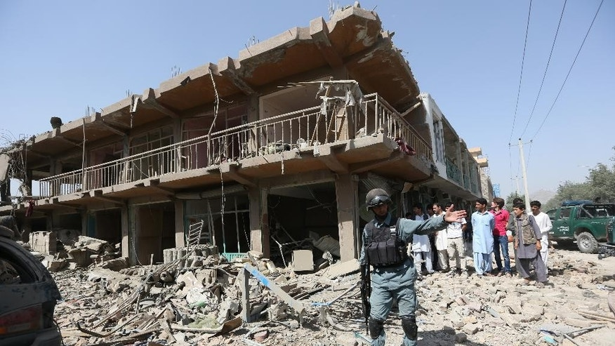 An Afghan police officer inspects the site of a car bomb attack in Kabul, Afghanistan, Friday, Aug. 7, 2015. A bomb hidden in a truck exploded in the center of the Afghan capital, killing several people and wounding hundreds, police and health officials said Friday. Police chief Abdul Rahman Rahimi said the pre-dawn blast was near a Defense Ministry compound, but that all of the victims were civilians, including women and children. (AP Photo/Rahmat Gul)