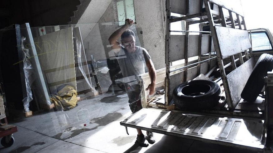 An employee of a glass products company carries a pane of glass in the industrial area of Sindos, a few kilometers west of the northern Greek port city of Thessaloniki, Friday, Aug. 7, 2015. The company is having difficulty paying overseas suppliers due to disruptions caused by capital controls in Greece. The government is racing to finalize a new bailout deal by Aug. 20 that would provide relief for the country's troubled banks. (AP Photo/Giannis Papanikos)