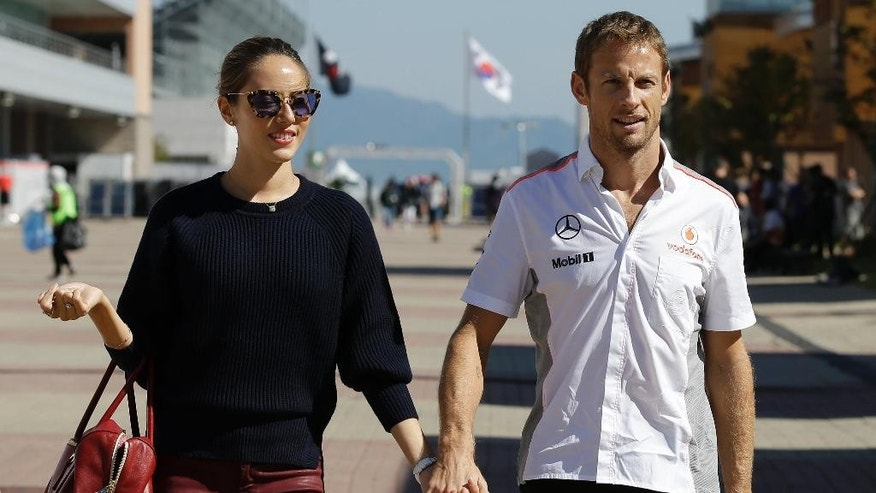 FILE - In this Thursday, Oct. 3, 2013 file photo McLaren Mercedes driver Jenson Button of Britain walks with Jessica Michibata down the F1 paddock as he arrives at the Korean International Circuit ahead of the Korean Formula One Grand Prix in Yeongam, South Korea. Burglars have ransacked the rented French Riviera villa of Formula One driver Jenson Button and his wife,  Jessica — possibly after pumping anaesthetic gas through air-conditioning vents. (AP Photo/Jin-man, File)