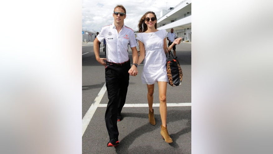 FILE - In this Thursday, Oct. 10, 2013 file photo McLaren driver Jenson Button of Britain, left, and Jessica Michibata walk down the F1 paddock at the Suzuka circuit, ahead of Sunday's Japanese Formula One Grand Prix, in Suzuka, Japan. Burglars have ransacked the rented French Riviera villa of Formula One driver Jenson Button and his wife,  Jessica — possibly after pumping anaesthetic gas through air-conditioning vents. (AP Photo/Shizuo Kambayashi, File)