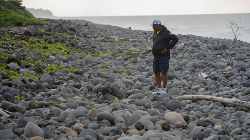 Aug. 6, 2015: An unidentified man walks on the beach of Saint-Andre, Reunion Island, in the hope of finding more plane debris. (AP Photo/Fabrice Wislez)