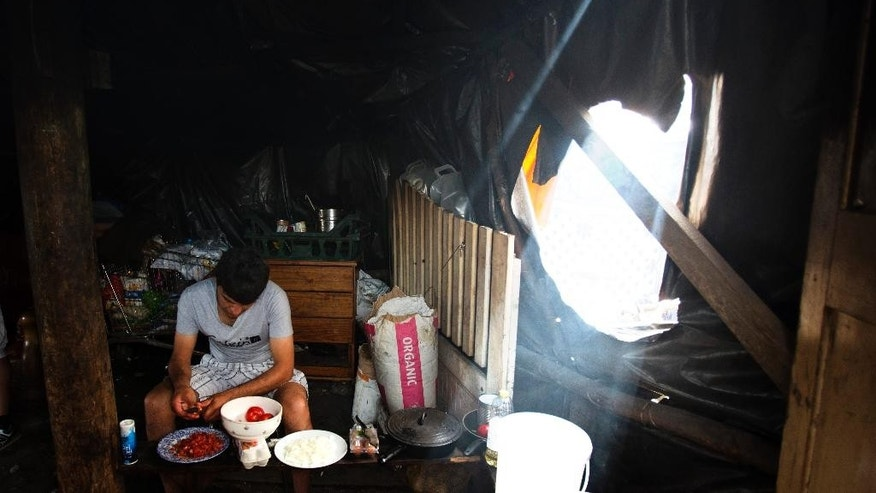 "In this Aug. 5, 2015 photo Afghan migrant Bahar Wafa, 25, prepares dinner for him and his friends inside a tent at a camp set near Calais, northern France. An estimated 2,500 migrants are currently at the windswept camp surrounded by sand dunes that sprung up when a state-approved day center for migrants was opened nearby. The ramshackle encampment of tents and lean-tos is referred to as the ""jungle,"" like the camps it replaced. (AP Photo/Emilio Morenatti)"