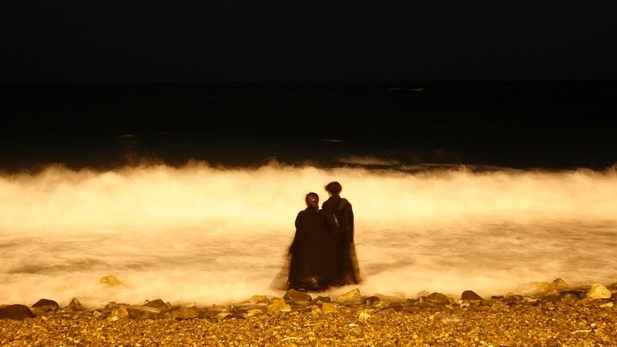 FILE - In this Dec. 26, 2007, file photo, two veiled Saudi women enjoy the Red Sea at night in Jiddah, Saudi Arabia. A video uploaded online in July 2015 that shows two young Saudi women being harassed by several young men on a seaside promenade in the coastal city of Jiddah has sparked a rare public debate on the rights of women in this ultra-conservative Muslim country that imposes a strict segregation of the sexes. (AP Photo/Hasan Sarbakhshian, File)