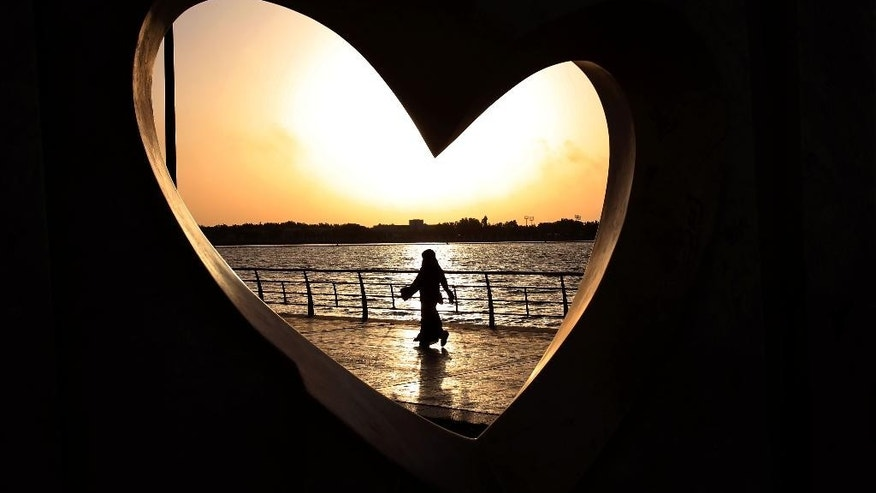FILE - In this May 11, 2014, file photo, a Saudi woman seen through a heart-shaped statue walks along an inlet of the Red Sea in Jiddah, Saudi Arabia. A video uploaded online in July 2015 that shows two young Saudi women being harassed by several young men on a seaside promenade in the coastal city of Jiddah has sparked a rare public debate on the rights of women in this ultra-conservative Muslim country that imposes a strict segregation of the sexes. (AP Photo/Hasan Jamali, File)