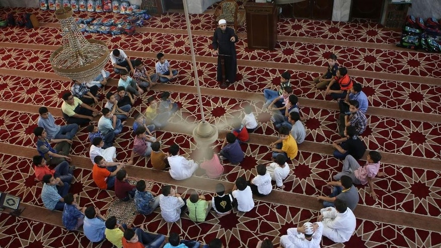 In this Sunday, Aug. 2, 2015 photo, Jordanian boys gather around an Imam at a mosque during a religious class in Amman, Jordan. The government says it's tackling the contradiction between official anti-extremist policy and what is taught in schools and mosques by rewriting school books and retraining thousands of teachers and preachers. Critics say the reforms are superficial, fail to challenge hard-line traditions, and that the first revised textbooks for elementary-school children still present Islam as the only true religion. (AP Photo/Raad Adayleh)