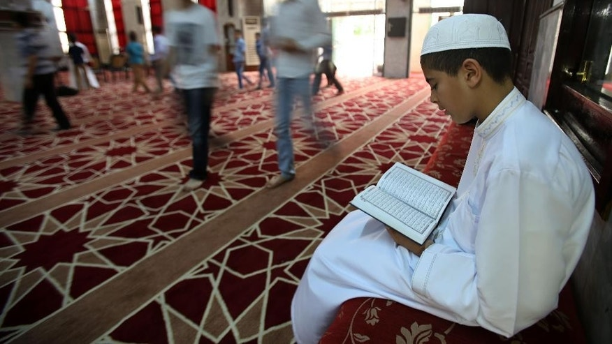 "In this Sunday, Aug. 2, 2015 photo, a Jordanian boy reads verses of the holy Quran before attending a religious class offered by an Imam at a mosque in Amman, Jordan. The country says it is re-educating mosque preachers and rewriting school books to stamp out Islamic extremism, as part of its ""war of ideas"" with Islamic State militants who control large areas of neighboring Syria and Iraq and pose a potential threat to the kingdom. (AP Photo/Raad Adayleh)"