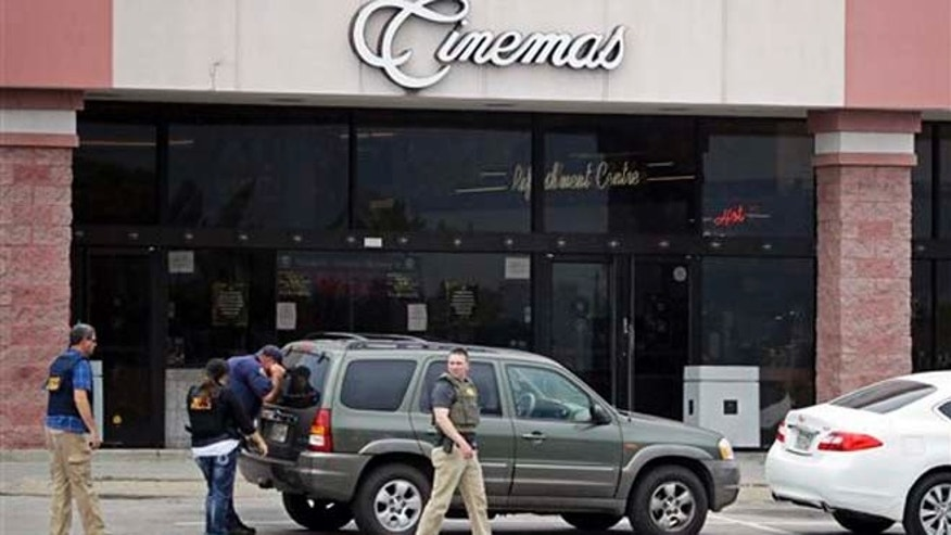 Police work outside a movie theater where officials reported a man was killed by police Wednesday, Aug. 5, 2015, in Antioch, Tenn. A man armed with a hatchet, gun and pepper spray unleashed a volley of the acidic chemical at theatergoers and exchanged fire with a responding police officer during a âMad Maxâ movie before being shot dead by a SWAT team as he tried to escape through the theaterâs rear door, police said. (AP Photo/Mark Humphrey)