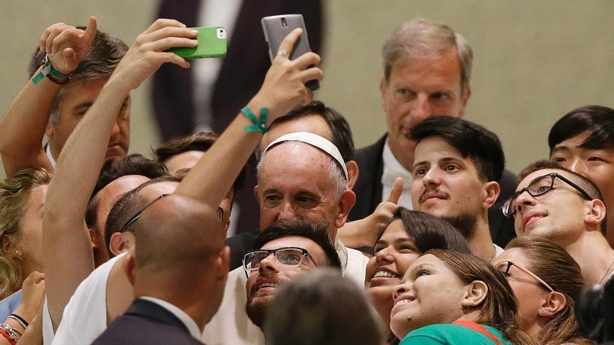 Pope Francis, center, poses for pictures during a meeting with the Eucharistic Youth Movement during am audience in the Paul VI hall at the Vatican, Friday, Aug. 7, 2015. (AP Photo/Gregorio Borgia)