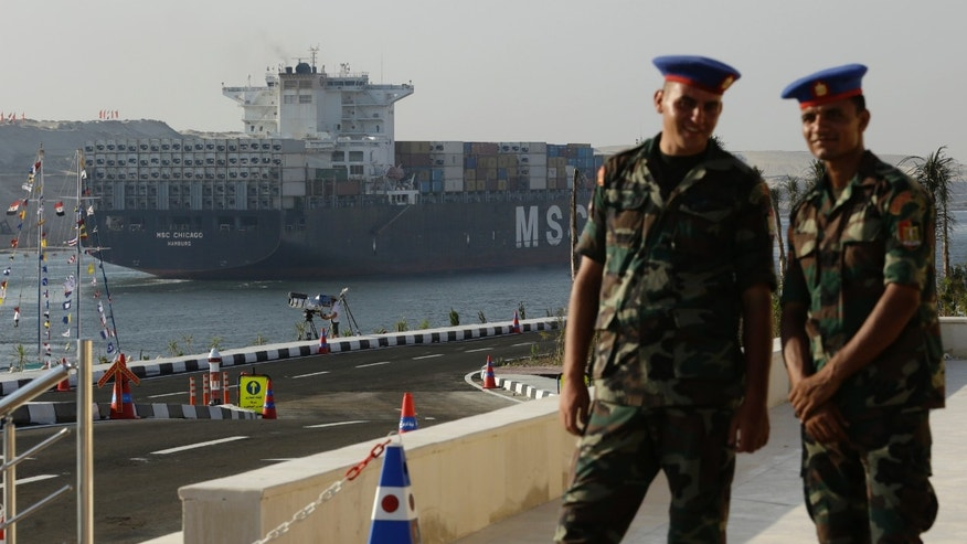 Aug. 6, 2015 - Egyptian army soldiers watch a cargo container ship cross the new section of the Suez Canal after the opening ceremony in Ismailia, Egypt. President Abdel-Fattah el-Sissi, has billed the canal extension as an historic achievement needed to boost the country's ailing economy.