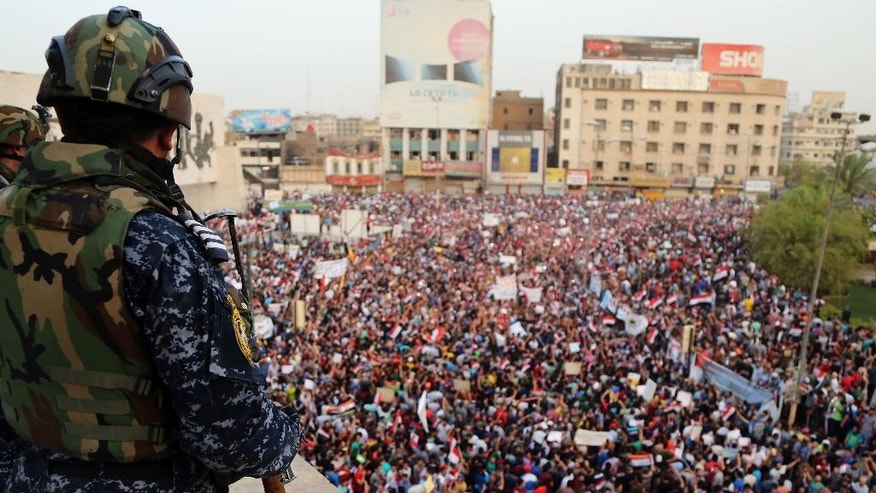 An Iraqi federal police officer stands guard while protesters chant anti-Iraqi government slogans during a protest in Tahrir Square in Baghdad, Iraq, Friday, Aug. 7, 2015. Thousands of Iraqis have braved the scorching summer heat to stage the protest in central Baghdad against government corruption. (AP Photo/Karim Kadim)