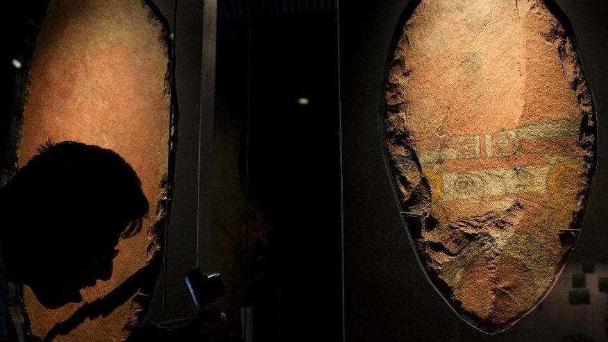 A man bends down to take a picture of a giant symbolic sacrificial knife, part of a display of items offered to the Aztec god Xochipilli, at the Templo Mayor museum in Mexico City, Friday, Aug. 7, 2015. The Aztecs usually sacrificed quails to Xochipilli, rather than still-beating human hearts. And he was worshipped at vast poetry and music festivals, rather than martial displays. (AP Photo/Rebecca Blackwell)