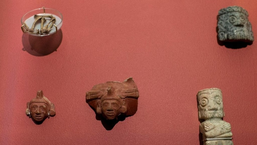 An image of the Aztec god Xochipilli, center, is part of a display of items used as offerings to the god, at the Templo Mayor museum in Mexico City, Friday, Aug. 7, 2015. In the pantheon of Mexico's pre-Hispanic gods, most Aztec dieties are depicted as brutal, blood-thirsty gods, only appeased by human sacrifices. But the Templo Mayor museum has put on display for the first time an offering dedicated to Xochipilli, the Aztec god of singing, dancing, and the morning sun. The offering was found in 1978 during excavations of the Red Temple, a small altar adjacent to Templo Mayor. (AP Photo/Rebecca Blackwell)